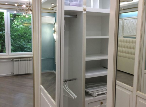 изготовление гардеробной комнаты на заказ с подвесными дверями-купе: фасады и наличники выполнены из МДФ с золотой патиной